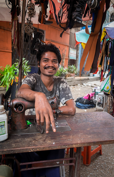 YANGON, MYANMAR - CIRCA DECEMBER 2013: Tailor offering alterations in the street market of Yangon