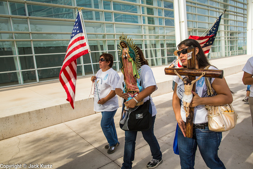 "19 JULY 2012 - PHOENIX, AZ:  People march around the US Courthouse on the first day of a class action lawsuit, Melendres v. Arpaio in Phoenix Thursday. The suit, brought by the ACLU and MALDEF in federal court against Maricopa County Sheriff Joe Arpaio, alleges a wide spread pattern of racial profiling during Arpaio's ""crime suppression sweeps"" that targeted undocumented immigrants. U.S. District Judge Murray Snow granted the case class action status opening it up to all Latinos stopped by Maricopa County Sheriff's Office deputies during the crime sweeps. The case is being heard in Judge Snow's court.  PHOTO BY JACK KURTZ"