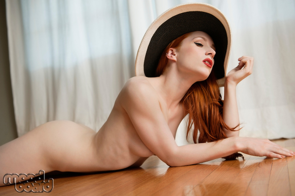 Young woman lying naked on wooden floor with a hat