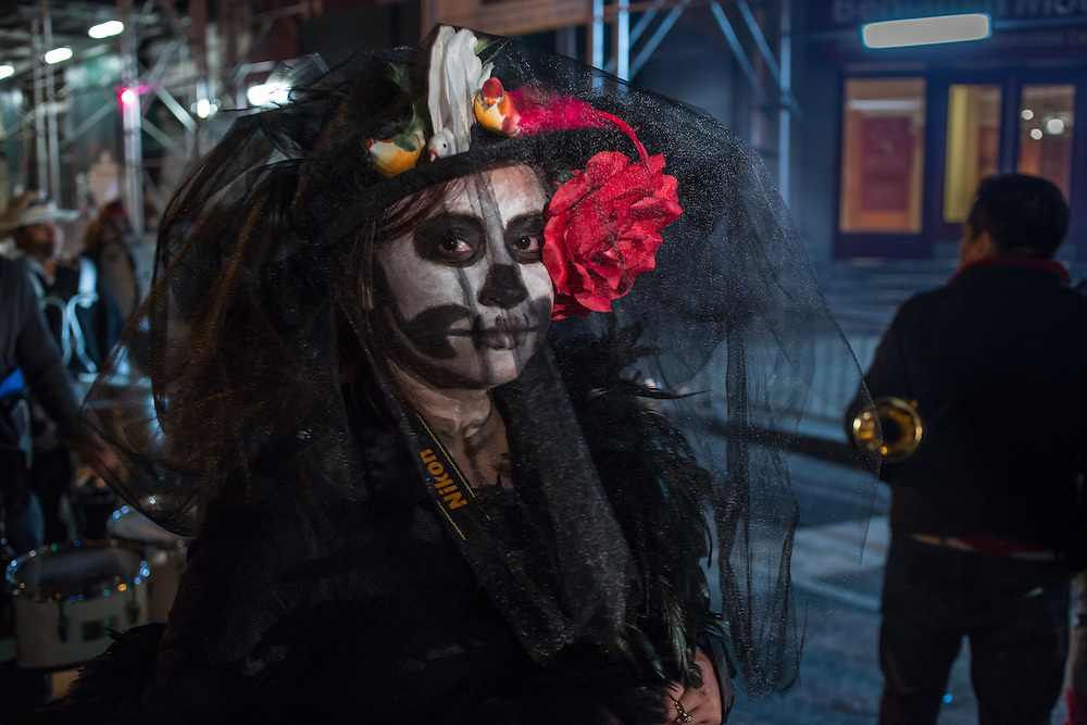 New York, NY - October 31, 2015. La Calavera Catarina wearing a hat decorated with birds, fruit, and a red flower, marching with the Aztec Marching Band.