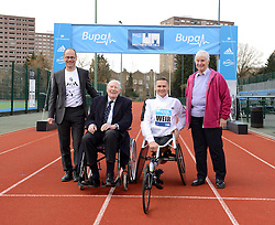 © London News Pictures. 26/02/2014. London, UK. L to R  HUGH BRASHER, Event Director, SIR ROGER BANNISTER, the first man to run a sub-four minute mile, DAVID IER, Paralympic wheelchair athlete, and DIANNE CHARLES (formerly Dianne Leather) the first woman to run a sub-five minute mile, at Paddington Recreation ground in London to launch the 2014 Bupa Westminster Mile in May 2014, which will officially celebrate the 60th anniversary. The track at Paddington Recreation ground was where Sir Roger Bannister trained for the record attempt. Photo credit: Mike King/LNP
