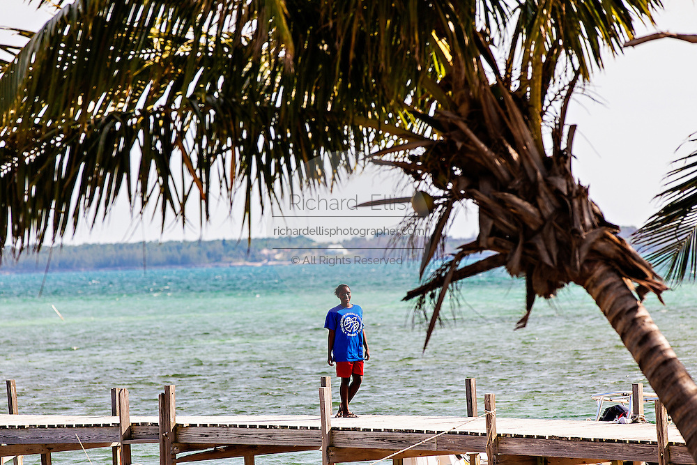 A young Bahamian girl walks along a doc past coconut palms on Green Turtle Cay, Bahamas.