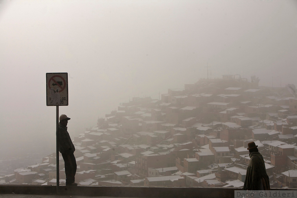 An Aymara woman walks up the hills that surround La Paz while a man waits for transportation on a chilly morning after a snow storm hit the world's highest capital on July, 26, 2007.(Dado Galdieri)