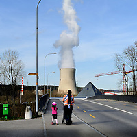 Mother with her children strolling along a road, with the cooling tower of the G&ouml;sgen Nuclear Power Plant (Kernkraftwerk G&ouml;sgen) rising behind. <br />