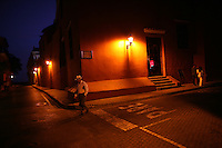 """A man crosses the street from the bar of the Santa Clara Hotel in the """"Old City"""" of Cartagena, a popular tourist destination on the Caribbean coast of Colombia. (Photo/Scott Dalton)"""