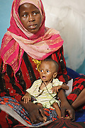 And woman holds her child, who suffers from acute malnutrition, at the UNICEF-sponsored Mao therapeutic feeding center in the town of Mao, Kanem region, Chad on Monday February 13, 2012.