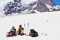 Climbers taking a rest break on the Muir snow field below Camp Muir, Mount Rainier, Washington, USA.