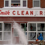"December 16, 2007 -- BATH, Maine. Raymond ""Buck"" Alexander blows snow from the sidewalk in front of his apartment, above the Frank Smith Cleaners in downtown Bath, on Sunday afternoon. ""A cop told me not to plow out in the road-- but then the plow guy came round and told me to go right ahead and put it out in the street. I'm goin' with the plow guy."" He added, ""I'm helpin' out the old lady who runs the shop downstairs. She's not quite so able as I am. And this thing (the electric snow blower) is awesome!"".Buck's fiancee, Sarah Rumery, right, and her daughters, Taylor Rumery, 3, left, and Madysin Rittall, 2, looked out the upstairs window with their neighbor Sarah Murphy, 22, as Buck cleaned up down below.  .""Do you want some hot chocolate?"" asked Sarah, Buck's fiancee, as Taylor and Madysin pushed snow off the window sill. Buck came upstairs and had a warm cup of cocoa after he finished up.  .Snow reached 10 inches deep in some places in Bath on Sunday.  On Sunday evening it rained, making an icy crust over the snow by dawn, as temperatures dropped into the teens.  Photo by Roger S. Duncan."