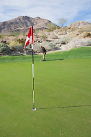 Senior man playing golf with flag in foreground