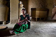 Pramila Tharu, 15, cradles her 2 year old toddler Prapti, as she sits at home in Bhaishahi village, Bardia, Western Nepal, on 29th June 2012. Pramila eloped and married at 12 and gave birth to Prapti at age 13. She delivered prematurely on the way to the hospital in an ox cart and her baby weighed only 1.5kg at birth. In Bardia, StC works with the district health office to build the capacity of female community health workers who are on the frontline of health service provision like ante-natal and post-natal care, especially in rural areas. Photo by Suzanne Lee for Save The Children UK