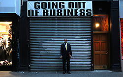 A man smokes outside a store that was closed down in New York, New York, USA, 20 October 2008. As Wall Street descend into a financial turmoil not seen since the stock market crash of 1929 and financial businesses were pommeled into rampant sell-offs in stocks and face regulatory changes to their business practices, professionals and non-professionals working in the district's banks, stock-trading houses and insurance companies are showing stress and a gloom not unlike the times of the Great Depression.