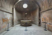 Labrum or marble basin, in an apse at the end of the caldarium or hot room, heated by a furnace, in the Forum Baths, in the Parco Archeologico di Pompei, or Archaeological Park of Pompeii, Campania, Italy. Pompeii was a Roman city which was buried in ash after the eruption of Vesuvius in 79 AD. The site is listed as a UNESCO World Heritage Site. Picture by Manuel Cohen