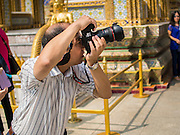 15 OCTOBER 2014 - BANGKOK, THAILAND:  A tourist uses a Canon digital camera in the Grand Palace in Bangkok. The number of tourists arriving in Thailand in July fell 10.9 per cent from a year earlier, according to data from the Department of Tourism. The drop in arrivals is being blamed on continued uncertainty about Thailand's political situation. The tourist sector accounts for about 10 per cent of the Thai economy and suffered its biggest drop in visitors in June - the first full month after the army took power on May 22. Arrivals for the year to date are down 10.7% over the same period last year.   PHOTO BY JACK KURTZ