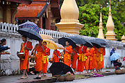 "Luang Prabang, Laos. Every morning at dawn, Buddhist monks walk down the streets collecting food alms from devout, kneeling Buddhists, and some tourists. They then return to their temples (also known as ""wats"") and eat together. This procession is called Tak Bat, or Making Merit."