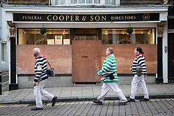 © Licensed to London News Pictures. 05/11/2016. Lewes, UK.  Revellers walk past a boarded up funeral directors in Lewes, East Sussex, ahead of the annual bonfire night parade. The celebrations, which mark the Guy Fawkes 1605 Gunpowder Plot to blow up Parliament, date back to the 1850s. Photo credit: Rob Pinney/LNP