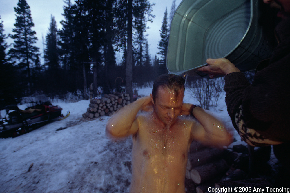 HAINES JUNCTION, BC- MARCH 02: Trapper Lance Goodwin bathes outside his cabin along his lynx trap line March 2, 2005 in Haines Junction, British Columbia. In 1999 the Colorado Division of Wildlife (CDOW) began a lynx reintroduction program, trapping the animals in Canada and bringing them to Colorado. The goal is to re-establish the lynx population in the state, which has been nonexistent since the 1970s, to a viable level where the population that can sustain itself. The program has brought in 204 lynx between 1999 and 2005. There have been 71 known deaths, and 101 kittens born. The program is considered widely as a success, however the program has also instigated controversy protests from animal rights groups and developers. (Photo by Amy Toensing). _________________________________<br /> <br /> For stock or print inquires, please email us at studio@moyer-toensing.com.