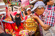 31 JANUARY 2014 - BANGKOK, THAILAND:   People make offerings to Chinese deities as they walk down Yaowarat Road during Lunar New Year festivities, also know as Tet and Chinese New Year, in Bangkok. This year is the Year of the Horse. Ethnic Chinese make up about 14% of Thailand and Chinese holidays are widely celebrated in Thailand.     PHOTO BY JACK KURTZ