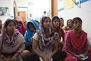 Garment workers listening during a session at a cafe meeting organised and hosted by Awaj Foundation, Dhaka, Bangladesh.<br /> <br /> Awaj Foundation was founded by Nazma Akter in 2003 to support and empower garment workers to negotiate safer and fairer working conditions in factories.