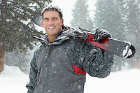 Young man holding skis in snow half length