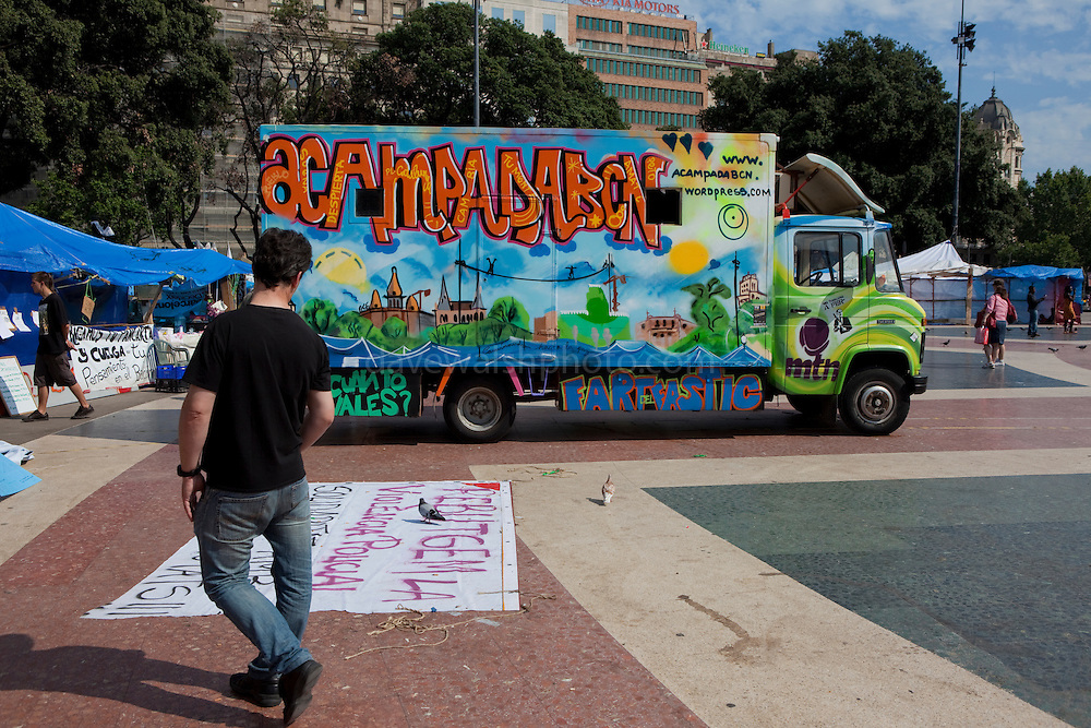 Man checks out poster at protest camp at Placa de Catalunya, Barcelona, Spain. The square has been relatively quiet since police attacked and beat antigovernment protestors on May 27 2011.