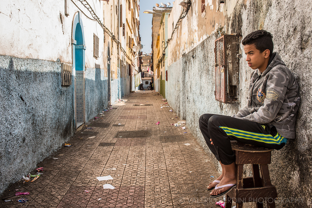 A boy sits at the entrance of a narrow street in the old medina of Casablanca