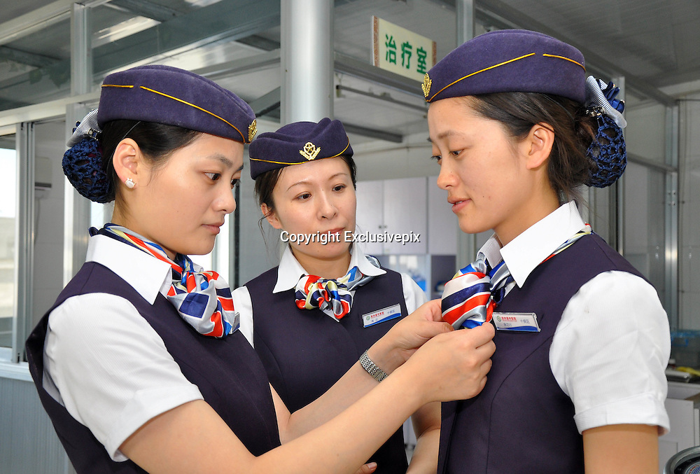 LIANSHUI, CHINA - MAY 15: (CHINA OUT) <br /> <br /> Nurses Dressed As Air Stewardesses <br /> <br /> A nurse dressed as air stewardess reads newspaper for a patient at Lianshui County Hospital of Traditional Chinese Medicine on May 15, 2014 in Lianshui county, Jiangsu Province of China. The Lianshui Huaian Hospital of Chinese Medicine has sent 12  nurses on an Eastern Airlines-style airline cabin crew training course and now requires them to wear air hostess uniforms on the wards. Bu Haijuan, the deputy chief Nurse, says the aim is to emphasise the personal service aspect of the hospital\'s care. <br /> &copy;Exclusivepix