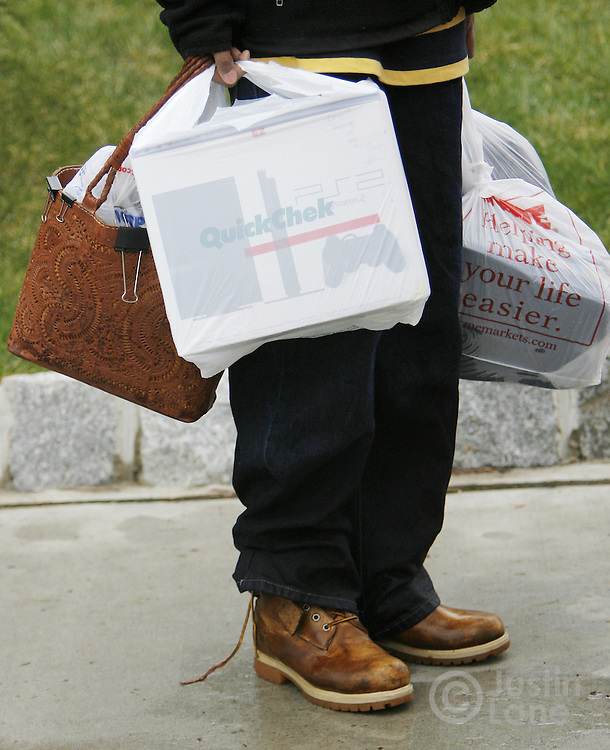 A resident of a flooded area of Bound Brook, New Jersey carries his essentials as he is evacuated, including a Sony Playstation 2, on Monday 16 April 2007. A large storm delivered records amount of rain to the East Coast of the United States over the weekend and today, causing New Jersey to declare a state of emergency.