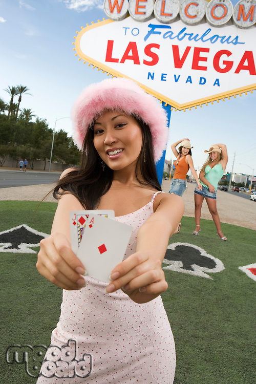 Woman holding cards in front of Las Vegas welcome sign, Nevada, USA