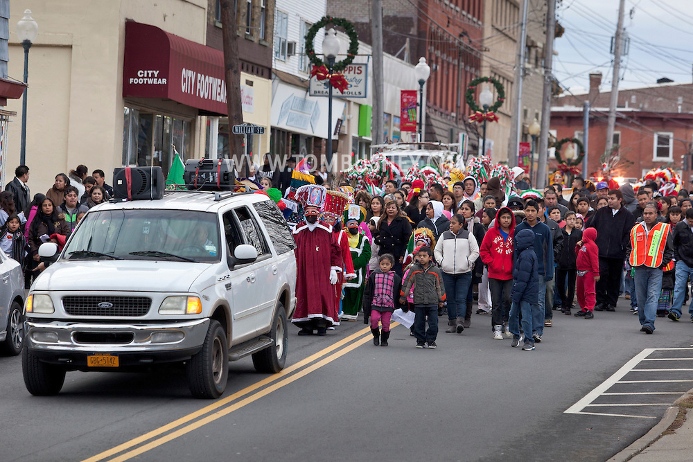 Middletown, New York - Members of St. Joseph's Church march through the city behind a vehicle playing music during the festival of Nuestra Senora de Guadalupe on Sunday, Dec. 9, 2012.