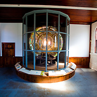 Twin Lights is situated 200 feet above sea level in Highlands, New Jersey.   Here the South Tower Fresnel lens exhibited in the building that housed the generating equipment for lighting the lens. The South Tower Fresnel lens may be seen during museum hours along with its clockwork mechanism.