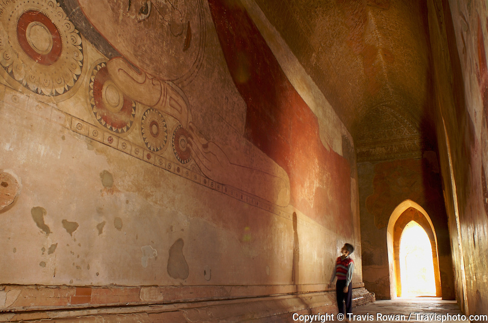 A child pauses to admire the massive buddhist murals in a temple in the Bagan region of Myanmar.