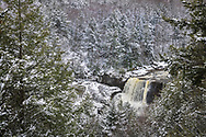 A fresh coat of snow peppers the pine trees framing the Blackwater Falls and creating a variegated textured winter wonderland landscape.