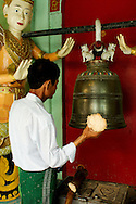 Man playing bell at Buddhist temple