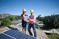 Two business people on a rooftop next to solar panelling  holding up a set of plans