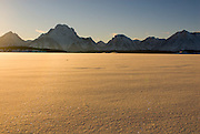 The Teton Range rises above a snow covered Jackson Lake in Grand Teton National Park, Jackson Hole, Wyoming.