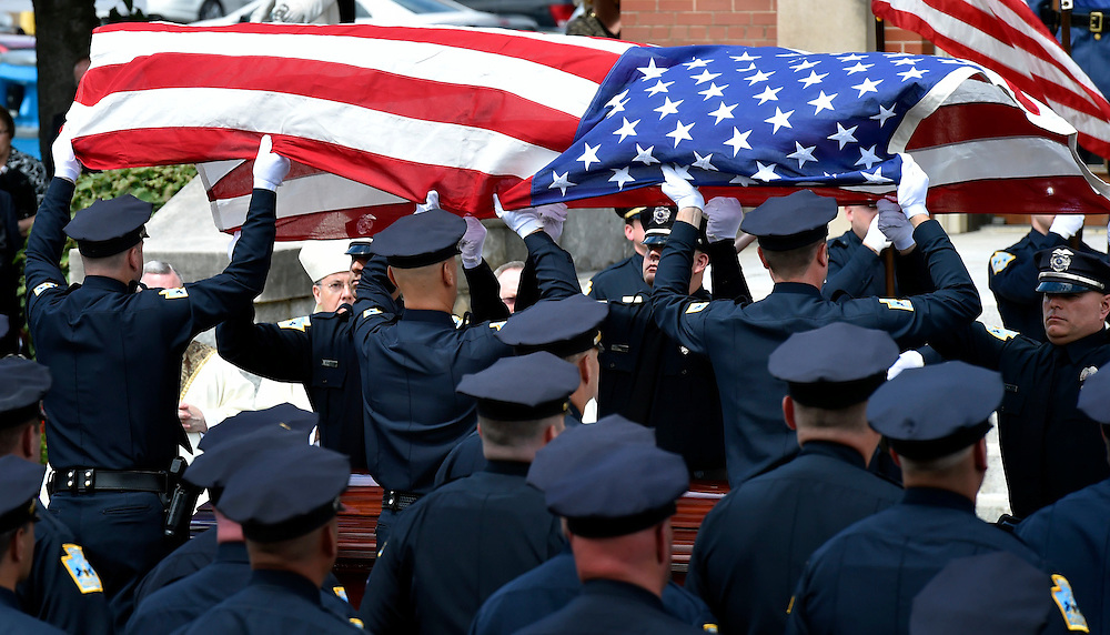 The flag from Officer John Wilding's casket is removed to be presented to his wife Kristen.