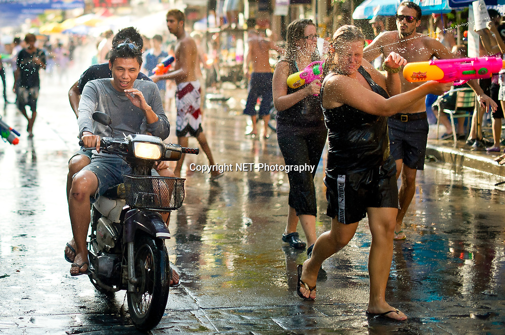 Locals and tourists spray each other with water guns during the Songkran festival at Khao San road, a popular tourist area in Bangkok. Songkran is the traditional Thai New Year festival. The most obvious celebration of Songkran is the throwing of water.