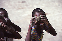 1986, Haiti --- Young boys smile as they look at the photographer through toy cameras they have made from clay.