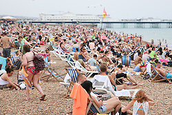 © Licensed to London News Pictures. 01/07/2015. Brighton, UK. Thousands of people Sunbathe on Brighton beach and swim in the sea on the hottest day of the year, today July 1st 2015. Photo credit : Hugo Michiels/LNP