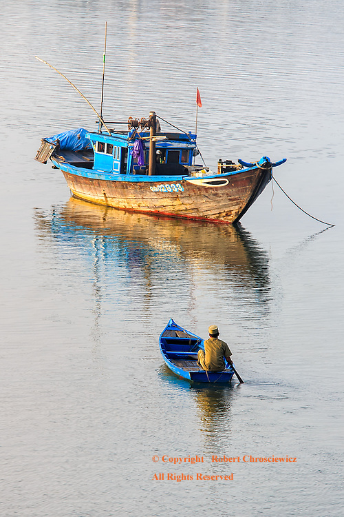 Morning Row: A man slowly rows out to his fishing boat in the early morning, Hoi An Vietnam.