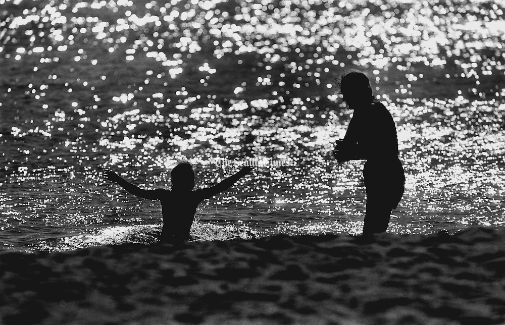 A child and her mother spend their afternoon catching rays and enjoying the beach near Golden Garden Park. (Chien-Chi Chang / The Seattle Times, 1990)