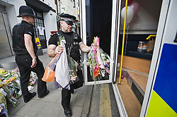 "© under license to London News Pictures.  28/03/2011. A police policeman removes flowers from outside SUJU nightclub in Swindon Wiltshire, where 22 year-old SIan O'Callaghan was last seen alive. The flowers where donated to local care homes. Christopher Halliwell has been charged with the murder of Sian O""Callaghan.  Photo credit should read: LNP.."