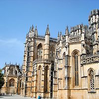 Batalha Monastery Lateral View in Batalha, Portugal<br /> This side view of the Monastery of Santa Maria de Vitória allows you to admire all of its splendid Gothic features which were constructed with limestone that has yellowed with age. You can see why it took about 130 years to build. This Dominican convent was finished in 1517 and became a UNESCO World Heritage Site in 1983.