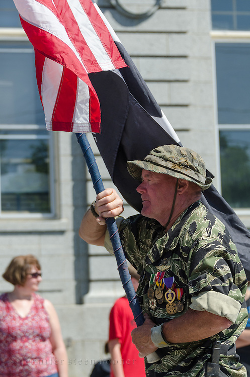 BAR HARBOR, MAINE, July 4, 2014. A veteran carries the US flag in the Independence Day Parade