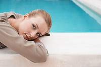 Women lying at edge of swimming pool portrait