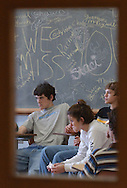 Fairfield High School juniors Cody Cole, Kristin Sorensen and Paul Reifschneider grieve as they recieve counseling Thursday afternoon as they sit in front of a chalkboard filled with students' signatures around the words 'We Miss You,' in memory of teacher Mike Beal. Beal died suddenly Wednesday evening from an apparent heart attack after jogging with his dog. (Travis Morisse, Jan. 15, 2004)