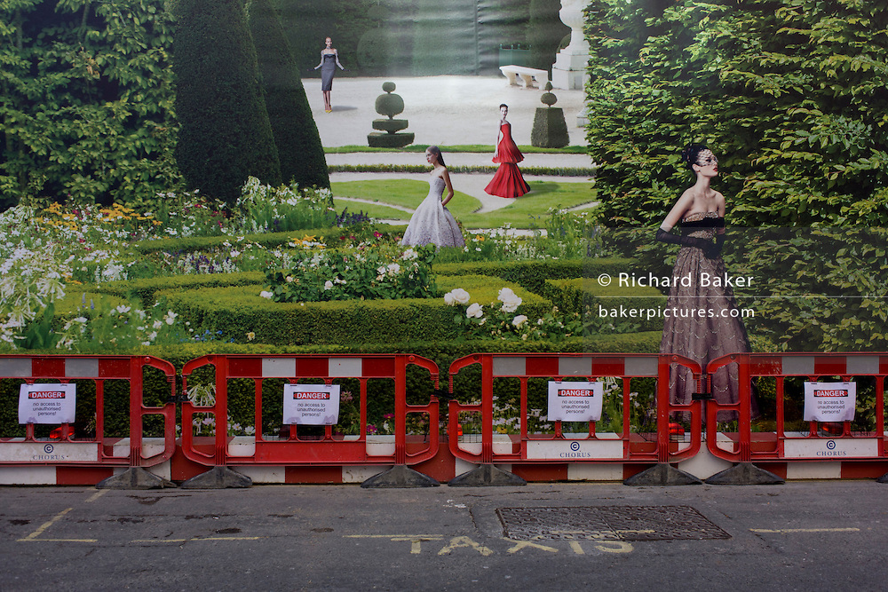 A background of hanging hoarding media, of a Dior shop being refurbished in central London.