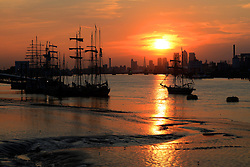 © Licensed to London News Pictures. 08/09/2014. London, England. The Sun sets over some of the Tall Ships at Woolwich Pier. Photo credit : Mike King/LNP
