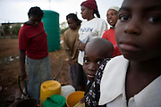 "Adults and Children in the suburb of Budiriro outside of Harare queue to collect clean water in containers brought to collection points where water bowsers have been supplied by NGO's such as UNICEF. ..As of 30 May 2009, there were 98 424 suspected cases, including 4 276 deaths reported by the Ministry of Health and Child Welfare (MoHCW) of Zimbabwe since August 2008. Fifty-five out of 62 districts in all 10 provinces were affected. in December 2008, Robert Mugabe declared that ""there is no cholera"" in Zimbabwe. Failing sanitation and lack of water supply were to blame, workers responsible claimed they had not been paid by the government for several months."
