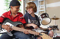 Two boys (10-12) with instruments in garage